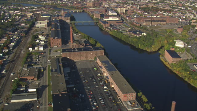 aerial mills and factories on merrimack riverbank with bridges nearby, and city center on the other bank / lowell, massachusetts, united states - lowell stock videos & royalty-free footage