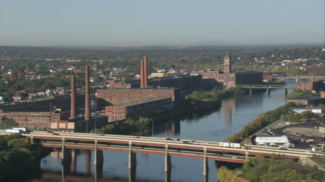 aerial mills and factories on merrimack riverbank with bridges nearby / lowell, massachusetts, united states - lowell stock videos & royalty-free footage