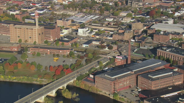 aerial mills and factories on merrimack riverbank with fall foliage and a bridge with traffic / lowell, massachusetts, united states - lowell stock videos & royalty-free footage