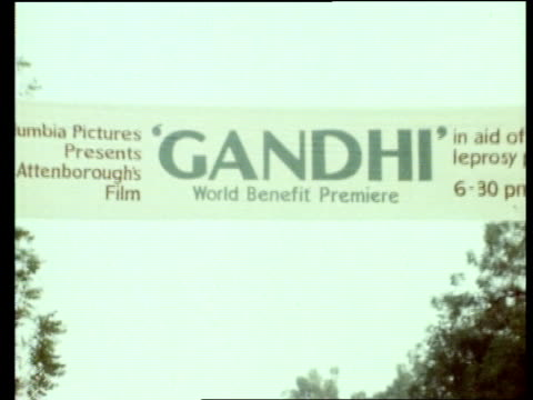 Intvw SOF Well it was interesting rather than a movie' LMS Policeman directing traffic 'Gandhi' hoarding above him ZOOM MS TILT Gandhi banner across...