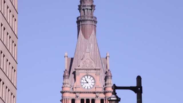 milwaukee city hall clock tower clock face 1044 american flag at halfmast on roof enclosed glass pedestrian overpass w/ unidentifiable person walking... - peshawar video stock e b–roll
