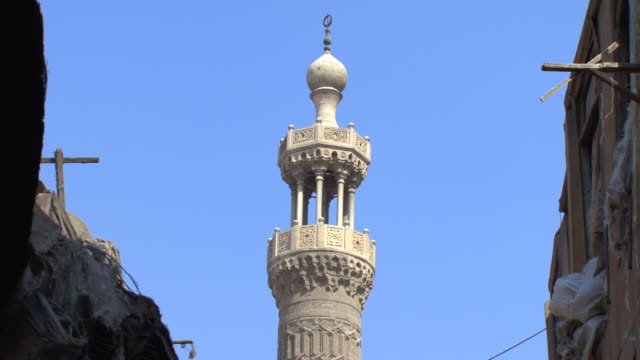 Minaret above Khan al Khalili souk, Cairo, Egypt - pan down to reveal busy bazaar below