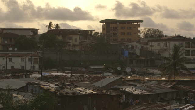 A minaret stands amongst corrugated iron rooves in Kenema, Sierra Leone, at dusk (matching light and dark shots).