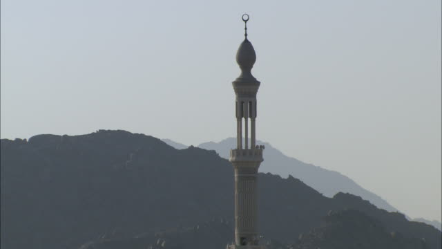 a minaret tops a grand mosque near a mountain. - grand mosque stock videos and b-roll footage