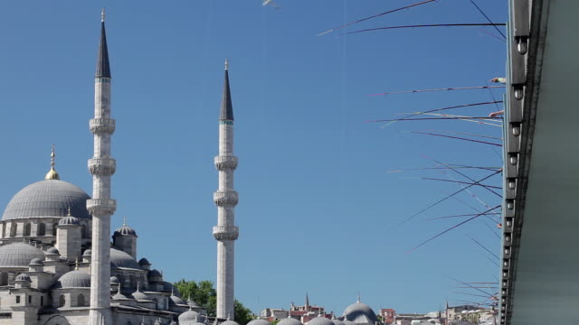 ms minarets of new mosque (yeni mosque) and fishing rods from galata bridge against blue sky / istanbul, turkey - yeni cami mosque stock videos and b-roll footage