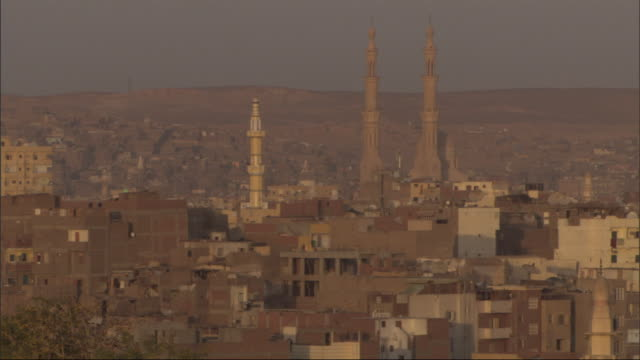 minarets rise high above multistory buildings in an egyptian city. - minareto video stock e b–roll