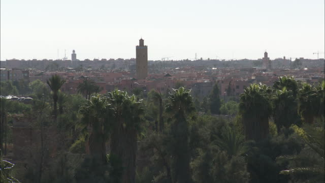 minarets tower over marrakech, morocco late in the day. - minaret bildbanksvideor och videomaterial från bakom kulisserna
