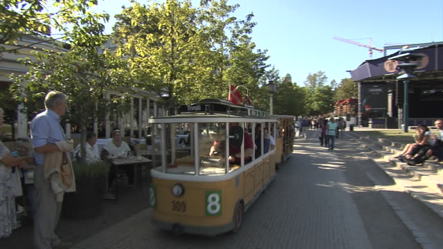 a minature replica trolley car transports people around the grounds of copenhagen's tivoli gardens. - copenhagen video stock e b–roll
