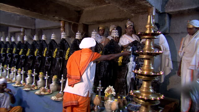 A minature statue of Bahubali is anointed with milk during the Jain festival of Mahamastakabhisheka. Available in HD.