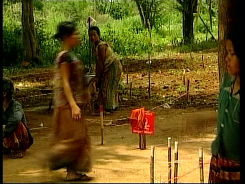 Mine field corruption ITN Woman sitting in hut winnowing grain in sieve EXT Mine signs in ground as hut beside Lee Huan interview SOT I had nothing...