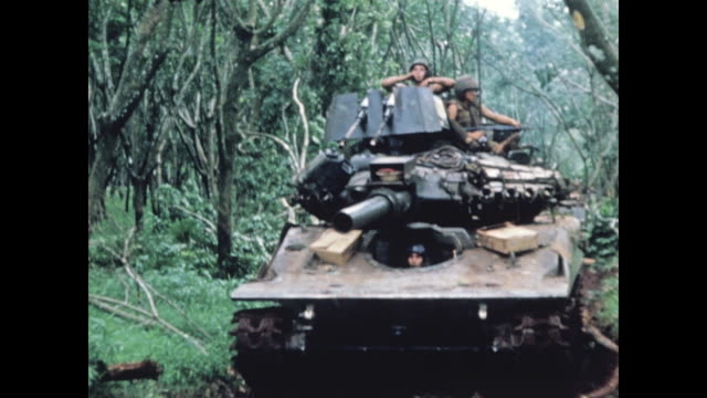 mine sweepers in front of tank then they approach / soldiers with mine detectors pass out of frame / tank gets bigger until it fills the frame and... - vietnamkrieg stock-videos und b-roll-filmmaterial