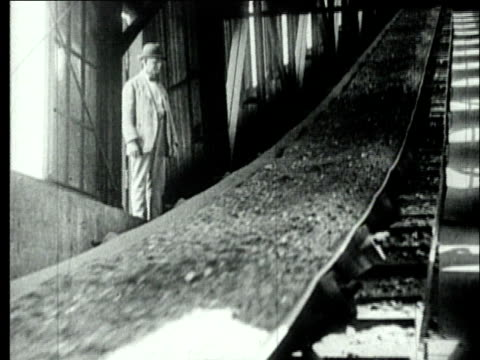 1927 b/w ms mine worker in suit watching coal moving up conveyor belt/ pennsylvania, usa - coal mine stock videos & royalty-free footage