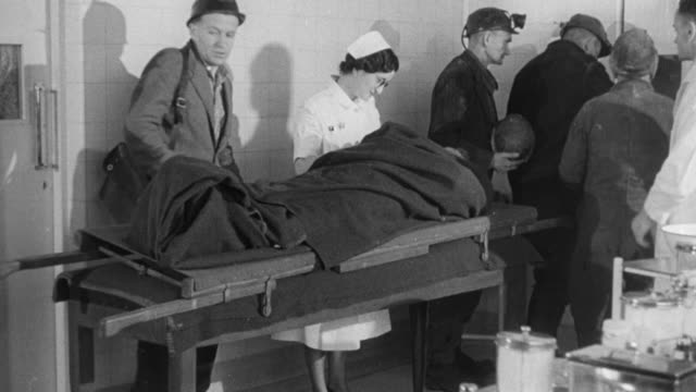 montage mine workers gathering around injured miner, worker in hospital, doctor examining patient and looking at x-ray / wales, united kingdom - injured stock videos & royalty-free footage
