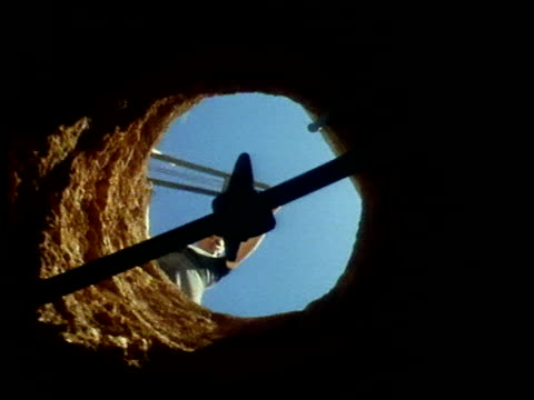 miner against circle of blue sky recedes as camera is lowered down mine shaft - mine shaft stock videos and b-roll footage