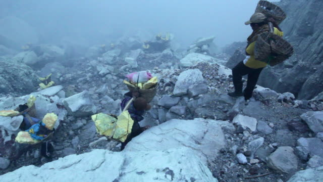 WS PAN Miner climbing the Ijen volcano crater carrying sulfur at early morning / Ijen, Java, Indonesia