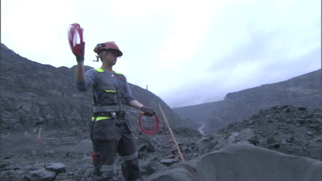 a miner places explosives into a pit at a surface mine. - sprengkörper stock-videos und b-roll-filmmaterial