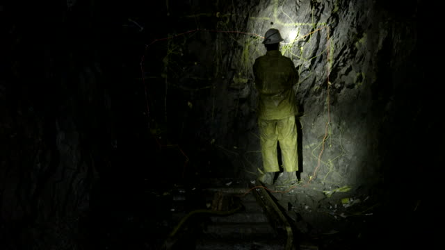 Miner sets detonating cords in mine tunnel