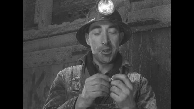 vidéos et rushes de miner sitting down and smoking cigarette takes off hard hat and brushes salt off clothes / miner rolling his own cigarette and lighting it with match... - lampe frontale