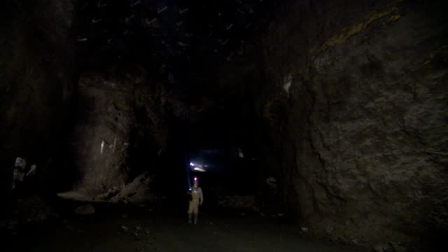a miner uses a flashlight to inspect the inside of a mine shaft. - mine shaft stock videos & royalty-free footage