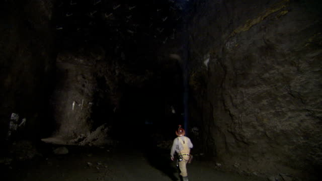 a miner uses a flashlight to inspect the inside of a mine shaft. - mining stock videos & royalty-free footage