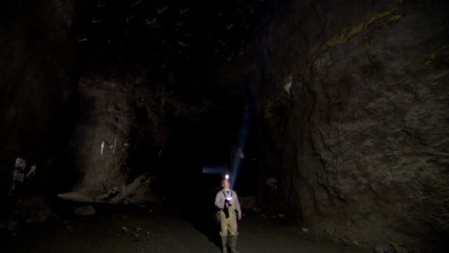 a miner uses a flashlight to inspect the inside of a mine-shaft. - mine shaft stock videos & royalty-free footage