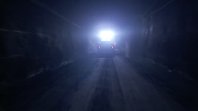a miner uses another vehicle's lights to navigate as he drives in a mine. - miner stock videos & royalty-free footage