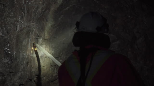 vidéos et rushes de cs of miner using rod to remove loose rocks - industrie minière