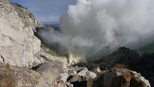 A miner walks past plumes of sulfuric gas rising from the Ijen volcano in Banyuwangi East Java Indonesia on Thursday June 2 A miner loads sulfur into...