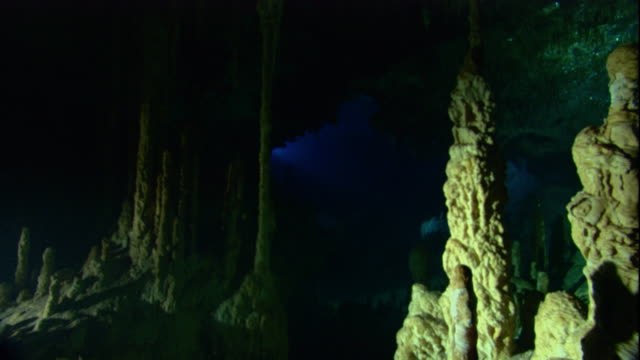 vídeos de stock, filmes e b-roll de mineral deposits form stalagmites in a flooded cenote cave in mexico. available in hd. - poço