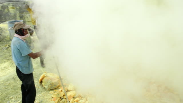 MS PAN Miners backing from the toxic clouds at the Ijen volcano crater / Ijen, Java, Indonesia