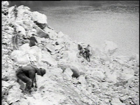 1921 montage miners cobbing the asbestos mines, the mine blasting, then miners gathering fiber after the blast / asbestos, quebec, canada - asbest stock-videos und b-roll-filmmaterial