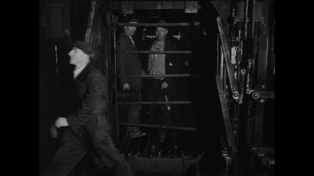 MONTAGE Miners descending the mine elevator / United Kingdom