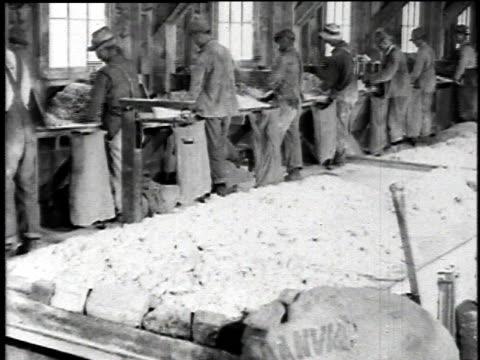 1921 MONTAGE Miners hammering ore rocks into finer gravel / Asbestos, Quebec, Canada
