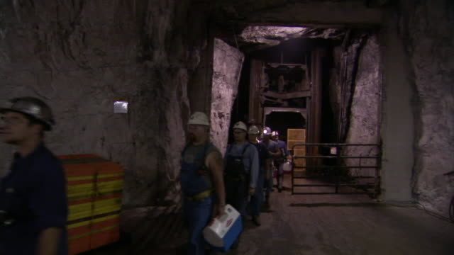 miners in hardhats carry lunch thermoses through a tunnel. - miner stock videos & royalty-free footage