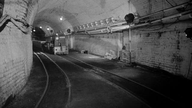 MONTAGE Miners operating locomotive underground, moving containers of coal along a track / Wales, United Kingdom