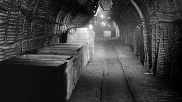 montage miners operating locomotives underground carrying tubs of coal traveling along a track / wales, united kingdom - bergwerk stock-videos und b-roll-filmmaterial