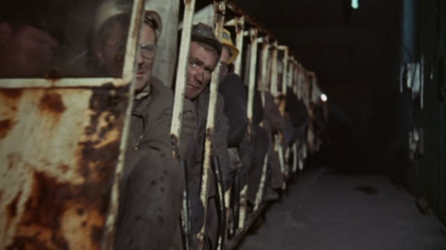 vidéos et rushes de 1973 pan miners riding underground transport vehicle / united kingdom - mineur de charbon