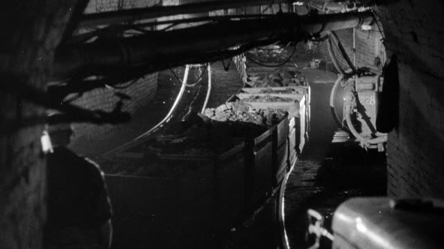 montage miners underground guiding containers of coal along a track / wales, united kingdom - miniera video stock e b–roll