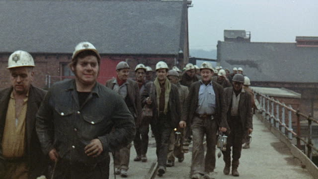 vidéos et rushes de 1971 montage miners walking across bridge outside mine / united kingdom - mineur de charbon