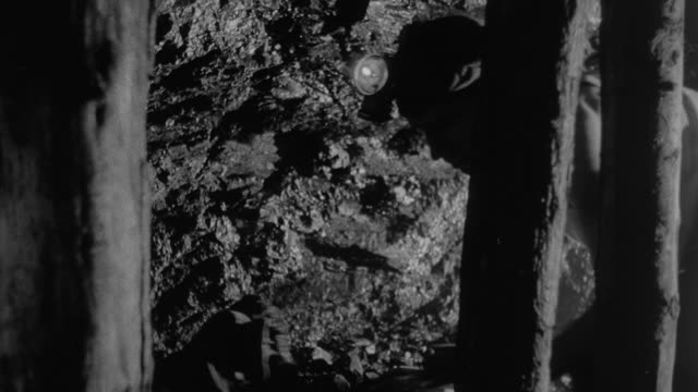 vidéos et rushes de 1978 montage miners working underground crawling and pickaxing by naked lights / united kingdom - charbon