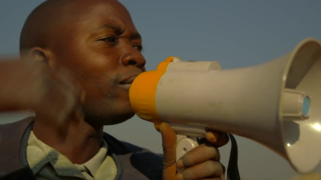 minesweeper from angola yells warning into megaphone close up - minesweeping stock videos & royalty-free footage