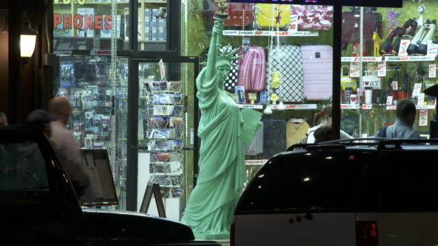 a mini statue of liberty sits outside of a novelty shop in new york city - statue of liberty new york city stock videos and b-roll footage