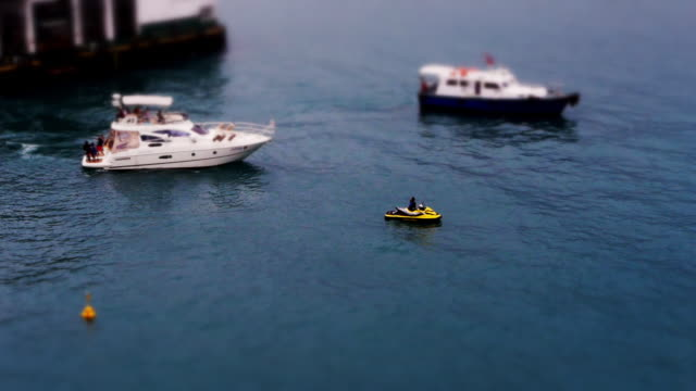 miniature boats and jetski in hong kong harbor - spoonfilm stock-videos und b-roll-filmmaterial