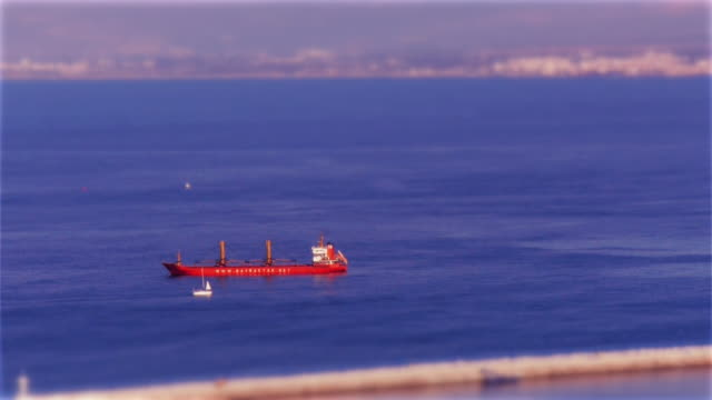 miniature effect tilt-shift: cargo ship and small sailboat passing - bay of water stock videos & royalty-free footage