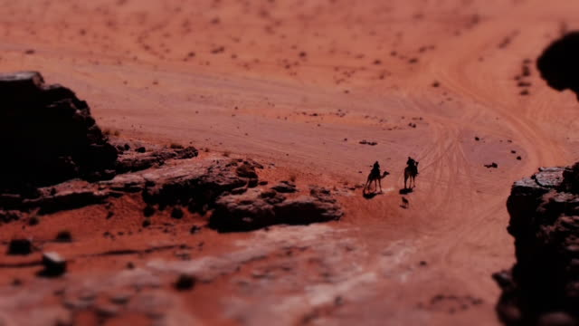 miniature effect - tiny bedouins on camels  in wadi rum desert, jordan, middle east. tilt-shift. - convoy stock videos and b-roll footage