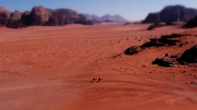miniature effect ws: tiny bedouins on camels passing through breathtaking desert scenery in wadi rum, jordan, middle east. tilt-shift. - middle east stock videos & royalty-free footage