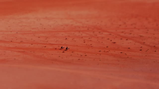 miniature effect: tiny bedouins on camels passing through desert in wadi rum, jordan, middle east. tilt-shift. - fake stock videos & royalty-free footage