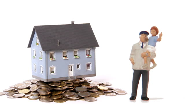 a miniature house is taken away from a leap of coins. - male likeness stock videos & royalty-free footage
