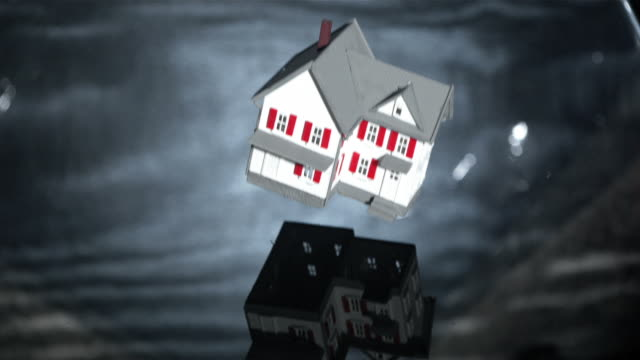 miniature model house falling into grey water - dollhouse stock videos & royalty-free footage