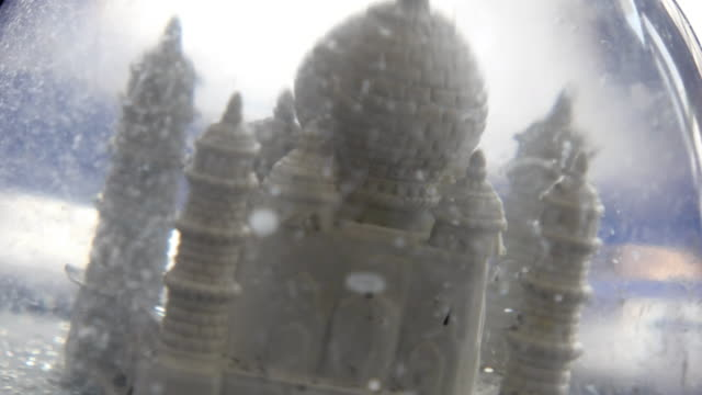 A miniature of Taj Mahal, a world heritage site, in a crystal balls with fake snow flakes.